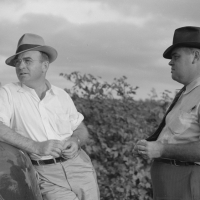 Mr. San Knowlton and one of his assistants, talking together in cotton field on Knowlton Plantation, Perthshire, Mississippi Delta, Mississippi. Marion Post Wolcott, 1939.