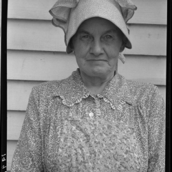 """Member of the congregation of Wheeley's church who is called """"Queen."""" She is wearing the old fashioned type of sunbonnet. Her dress and apron were made at home. Near Gordonton, North Carolina. July, 1939."""