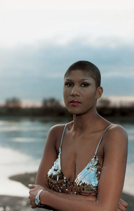 A color photo of a black woman with a close-cropped hair cut, wearing a silver sequined strappy top. She is in front of a body of water.